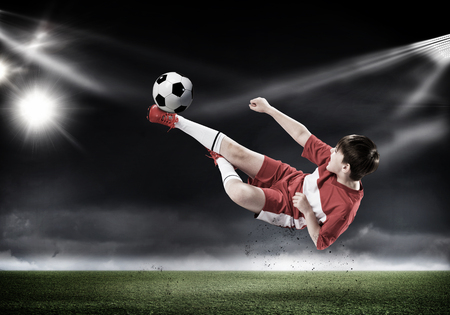 kid feet: Kid boy kicking soccer ball at stadium field