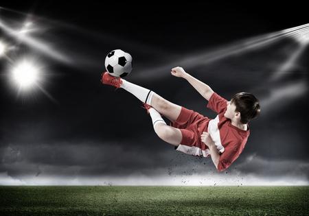pies masculinos: Muchacho del cabrito que golpea el balón de fútbol en campo del estadio