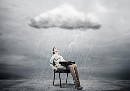 sotto la pioggia: Giovane donna di affari con la valigia seduta sulla sedia sotto la pioggia