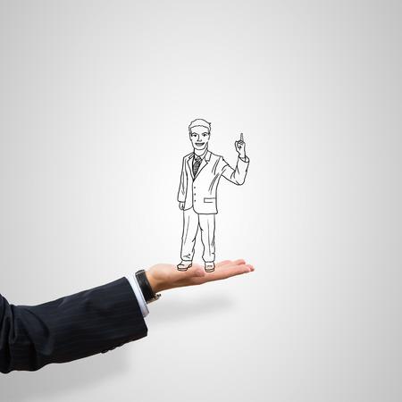 caricatura: hombre de negocios dibujado en la palma masculina sobre fondo gris Foto de archivo