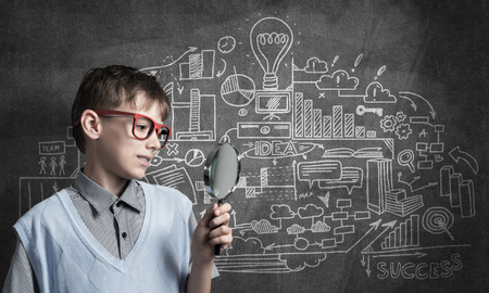 schoolkid search: Cute boy looking through magnifying glass against blackboard background Stock Photo