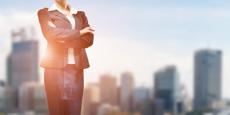 Close up of businesswoman with arms crossed on chest on modern city background Stock Photo