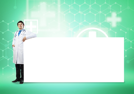 color therapist: Young handsome doctor with white blank banner. Place your text