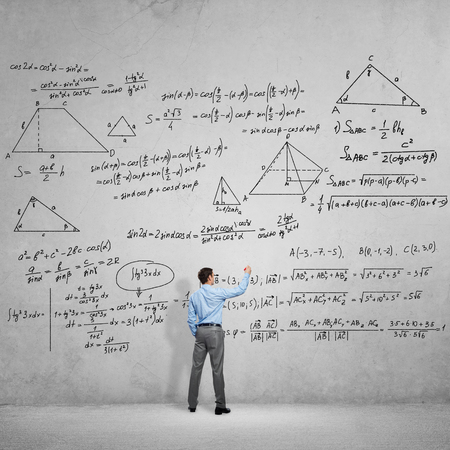 adult student: Rear view of man student or teacher drawing formulas on concrete wall