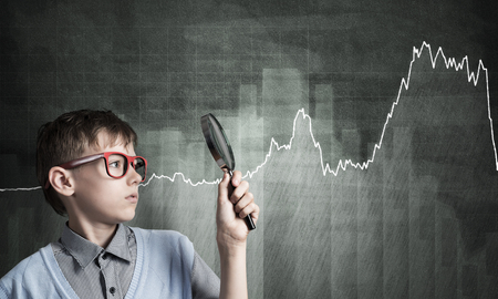 schoolkid search: Cute boy looking through magnifying glass against graphs at chalkboard