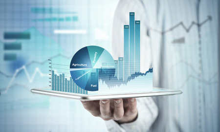Close view of businessman with tablet and graphs and charts on screen Stock Photo