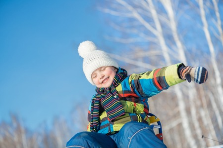 sledging people: Little cute boy riding sled in winter park