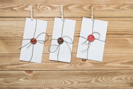 paper sheets: Envelope hanging on rope on wooden background