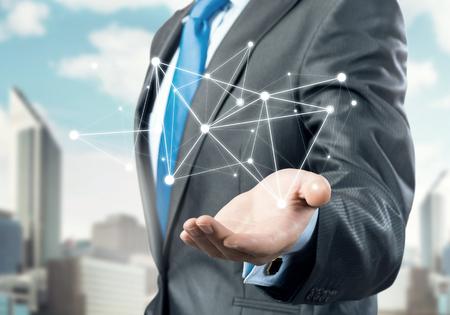 network connection: Businessman hand showing digital connection lines on city landscape