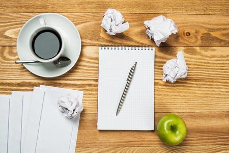 persona escribiendo: Vista superior del concepto de escritura creativa con los papeles en la mesa de madera