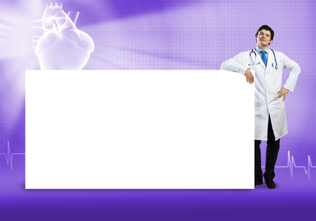 handsome doctor: Young handsome doctor with white blank banner. Place your text