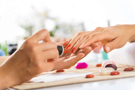 nails woman: Woman in salon receiving manicure by nail beautician