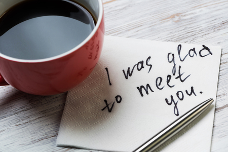 Cup of coffee and napkin with i was glad to meet you message on wooden table
