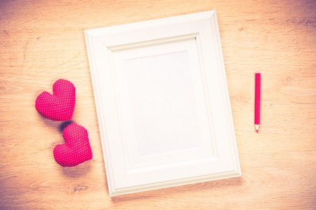 color photo: White photo frame small red hearts and pencil on wooden table