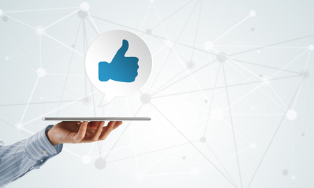 socially: Hand of businessman holding social network thumbs up icon
