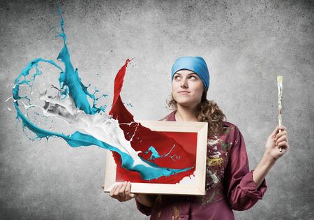 artista de la mujer bastante joven con el pincel en la mano