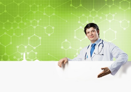 handsome doctor: Young handsome doctor holding white blank banner. Stock Photo