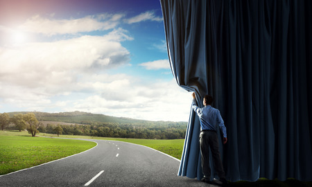 Businessman opening velvet curtain to countryside road Фото со стока