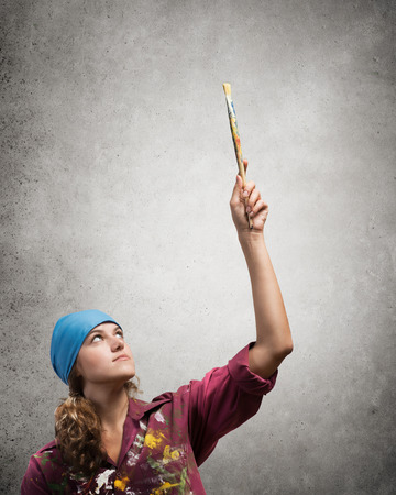 brush in: Young pretty artist woman with paint brush in hand