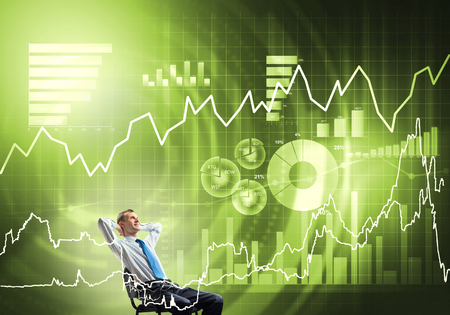 Young businessman sitting on chair with hands on head looking at virtual panel Stock Photo