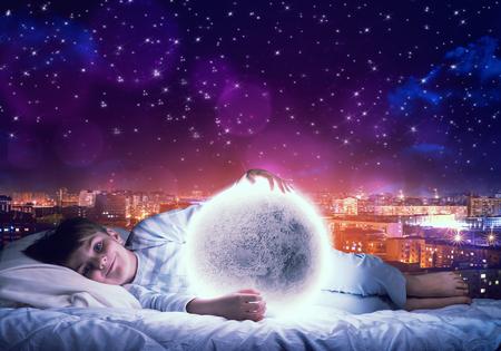 noche y luna: muchacho lindo en la cama mirando al planeta Luna resplandeciente. Elementos de esta imagen proporcionada por la NASA se Foto de archivo