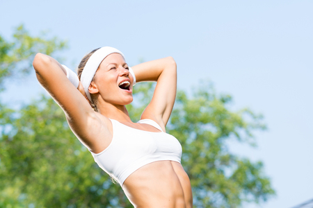 suntanned: Young sport woman enjoying weather in sunny park