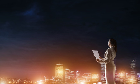 night vision: Rear view of elegant businesswoman with paper sheet against night city