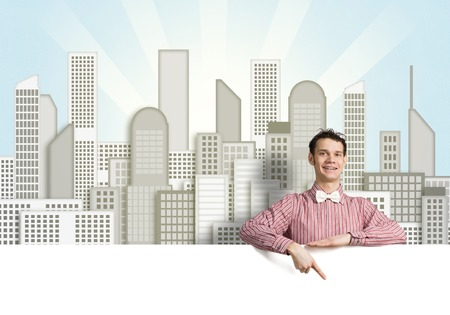 Young funny guy in checked shirt pointing with finger at  blank banner Stock Photo