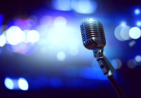 Close up of microphone in concert hall with blurred lights at background Stock Photo