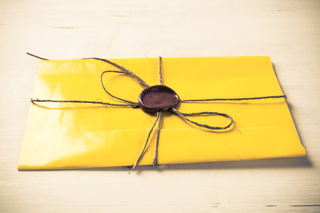 Yellow letter envelope with wax seal on wooden surface