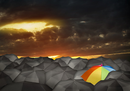 Conceptual image with colorful umbrella among many black ones Stock Photo