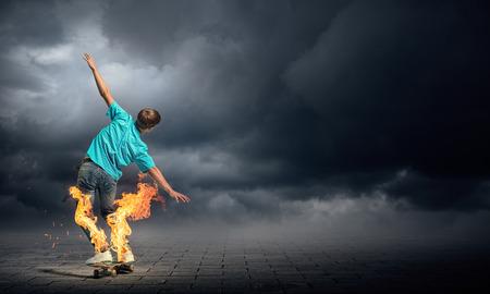 skateboarder: Skater boy riding on his skateboard burning in fire Stock Photo