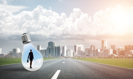 Young businesswoman trapped inside of light bulb on asphalt road Stock Photo