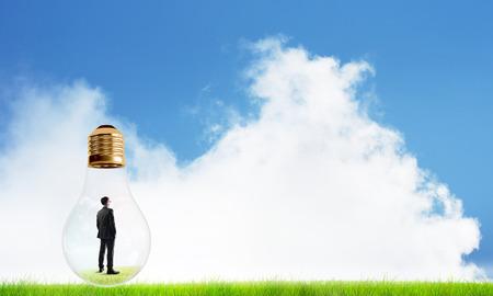 Businessman inside glass light bulb outdoors looking away Stock Photo