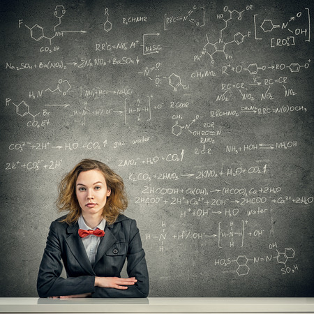 disheveled: Young woman with disheveled hair against blackboard background