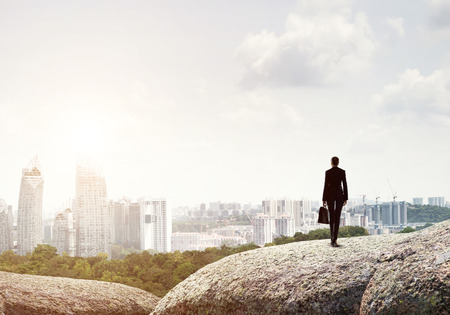 Businesswoman standing with back on top of hill and viewing modern city