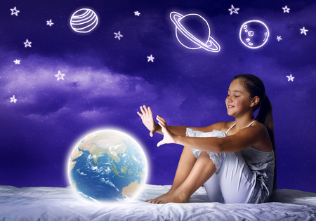 glowing earth: Cute girl in bed looking at glowing Earth planet. Elements of this image are furnished by NASA Stock Photo