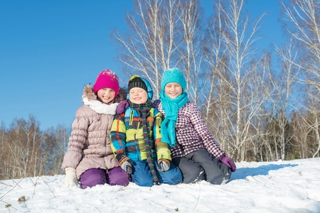 Three happy kids having fun in winter park