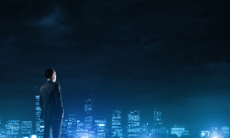 Elegant businessman with suitcase looking at night city Stock Photo
