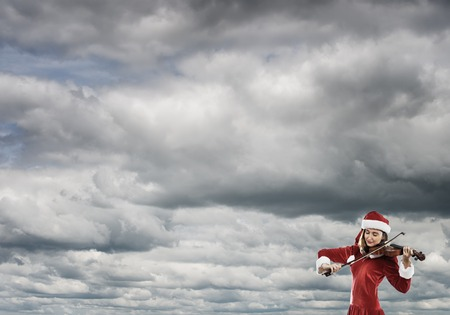 santa suit: Attractive young woman in Santa suit playing violin