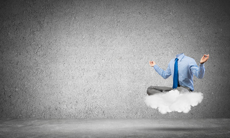 unknown men: Headless businessman sitting on cloud in lotus pose and meditating Stock Photo