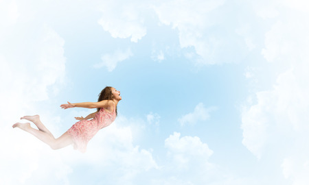 weightless: Young woman flying high in blue sky