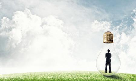 viewing: Businessman inside glass light bulb outdoors looking away Stock Photo