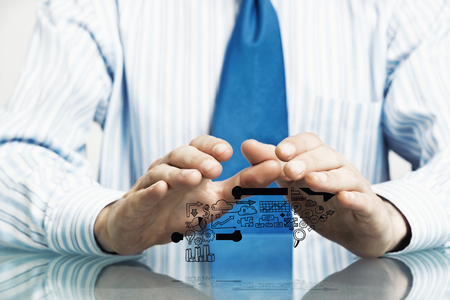 Businessman in suit sitting at desk making protective gesture with palms Stock Photo