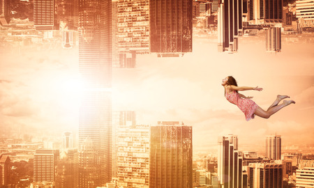 weightlessness: Young woman flying between two reality worlds Stock Photo