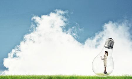 bulb fields: Businesswoman inside glass light bulb outdoors looking away