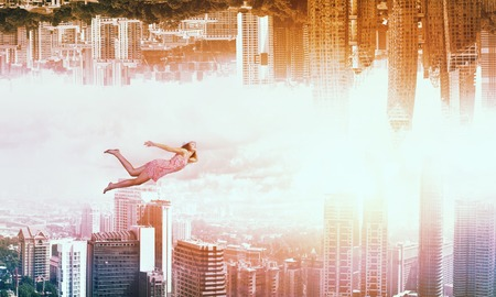 Young woman flying between two reality worlds Stock Photo