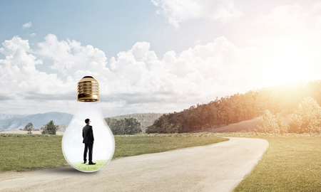 trapped: Young businessman trapped inside of light bulb on countryside road