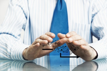 gesturing: Businessman in suit sitting at desk making protective gesture with palms Stock Photo
