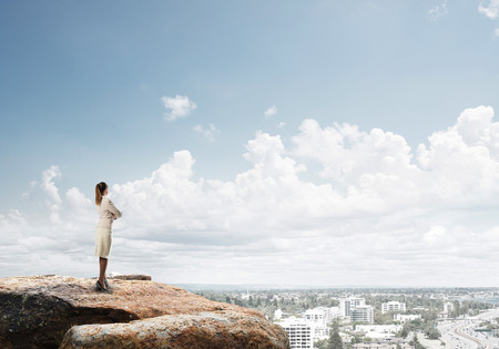to observer: Businesswoman standing with back on top of hill and viewing modern city